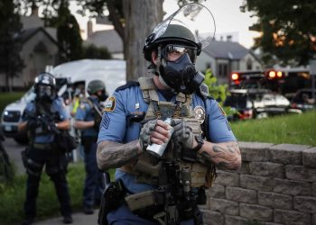 A police officer prepares to throw a tear gas canister towards protestors, Thursday, May 28, 2020, in St. Paul, Minn. Protests over the death of George Floyd, a black man who died in police custody Monday, broke out in Minneapolis for a third straight night. (AP Photo/John Minchillo)