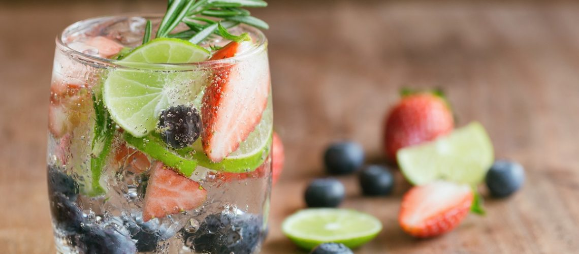 Infused water made from blueberry strawberry and lemon in sparkling mineral water look so freshness and healthy. Mixed fruit mojito on wood table with copy space. Summer refreshing drink concept. Ice blueberry soda in clear glass for summer.